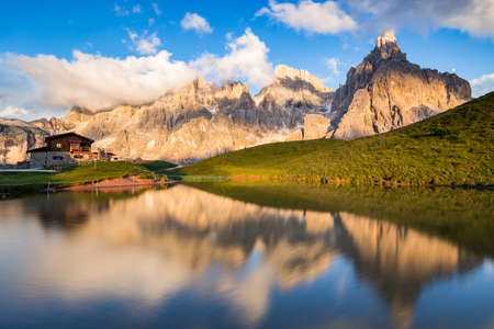 The Pale di San Martino peaks (Italian Dolomites) reflected in the water at sunset, with an alpine chalet on background.