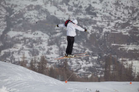A free-ride ski jumper, with skis crossed against a mountains photo