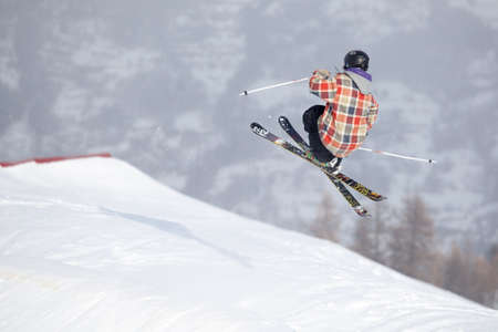 freeride: A free-ride ski jumper, with skis crossed against a mountains