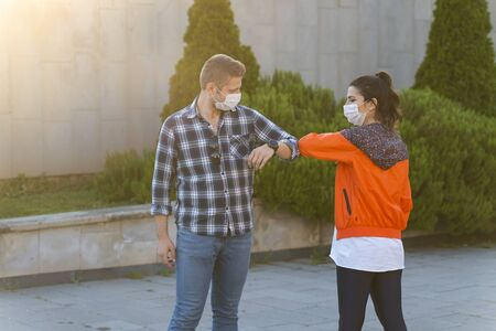 Friends in protective medical mask on his face greet their elbows in quarantine. Elbow bump. Coronavirus, illness, quarantine, medical mask, COVID19. 스톡 콘텐츠