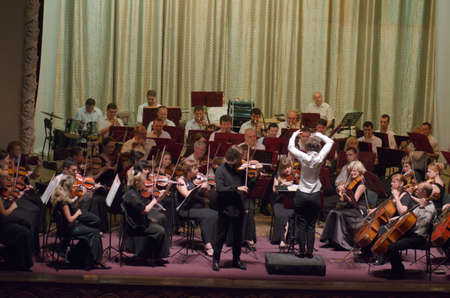 ensemble: DNIPRO, UKRAINE - JULY 1, 2016: Famous Violinist Dmitry Tkachenko and Academic Symphony Orchestra - main conductor Natalia Ponomarchuk perform at the Potemkin Palace. Editorial
