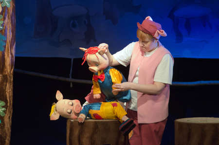 customary: DNIPROPETROVSK, UKRAINE - APRIL 3, 2016: Three pigletsperformed by members of the Dnipropetrovsk Puppet Theatre.