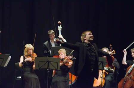 vibrate: DNIPROPETROVSK, UKRAINE - MAY 14: Famous violinist Ostap Shutko and members of the Symphony Orchestra perform at the State Russian Drama Theatre on May 14, 2015 in Dnipropetrovsk, Ukraine