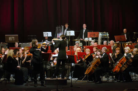 vibrate: DNIPROPETROVSK, UKRAINE - FEBRUARY 9: Famous Violinist Dmitry Tkachenko and Academic Symphony Orchestra perform at the State Russian Drama Theatre on February 9, 2015 in Dnipropetrovsk, Ukraine