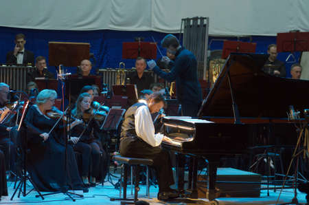 DNIPRO, UKRAINE - OCTOBER 8, 2016: American composer and pianist Calvin Jones and members of the Dnipro Symphonic Orchestra perform at the Philharmonic.