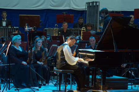 symphonic: DNIPRO, UKRAINE - OCTOBER 8, 2016: American composer and pianist Calvin Jones and members of the Dnipro Symphonic Orchestra perform at the Philharmonic.