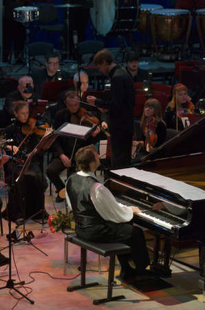 vibrate: DNIPRO, UKRAINE - OCTOBER 8, 2016: American composer and pianist Calvin Jones and members of the Dnipro Symphonic Orchestra perform at the Philharmonic.