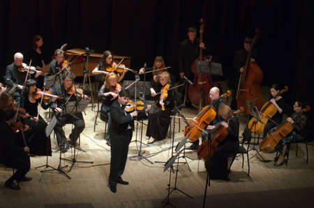 ensemble: DNIPRO, UKRAINE - JANUARY 30, 2017: Famous violinist Eugene Kostritsky and members of the FOUR SEASONS Chamber Orchestra perform at the State Drama Theatre.