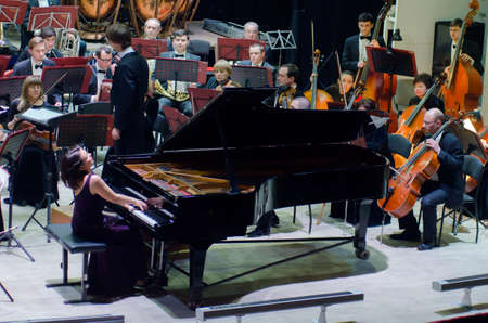 DNIPRO, UKRAINE - FEBRUARY 18, 2017: Famous Pianist Kateryna Titova and Academic Symphony Orchestra - main conductor Ivan Cherednichenko perform at the PhilharmoniÑ.