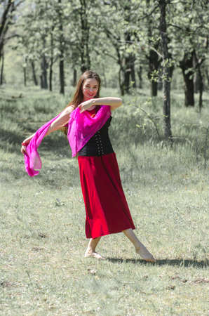 Beautiful young girl with long hair in a red dress is dancing in the forest.