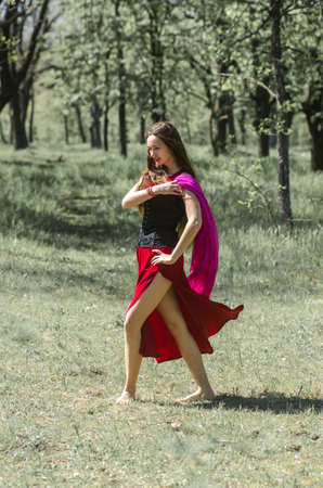 Beautiful young girl with long hair in a red dress is dancing in the forest. Foto de archivo