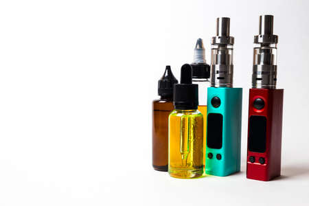 e- liquid, e-juice in the bottles and e-cigarette (vape) isolated on the white background with copyspace Stock Photo