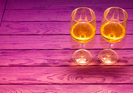 White wine in the wineglass on the purple wood background Stock Photo