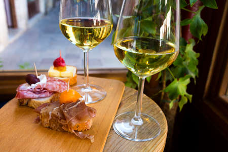 Different kind of the Cicchetti - italian tapas, small snacks with prosciutto, brie cheese, seafood, meat and other stuffing with two wine glasses of white wine