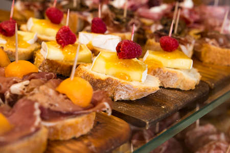 Different kind of the Cicchetti - italian tapas, small snacks with prosciutto, brie cheese, seafood, meat and other stuffing