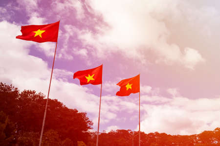 several flag of Vietnam on the flagpole with the blue cloudy sky in sun rays