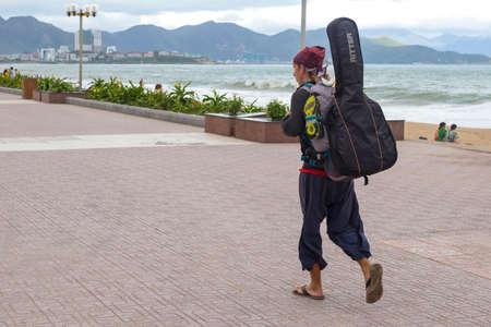 wandering vagabond musician goes near the sea towards the mountains, Vietnam, Nha Trang city 2018-01-10 Editorial