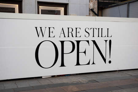 """inscription """"We are still open"""" on the street of Madrid, Spain 2018-08-05 Editorial"""