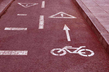 bike path (bicycle lane) sign on the road of the city (red toned, concept of dangerous) Stock Photo