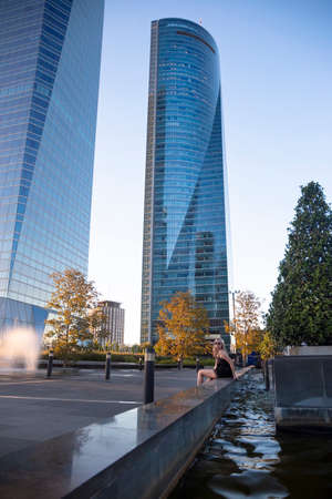Blonde girl near the Four modern skyscrapers (Cuatro Torres) in business financial district of Madrid, Spain 2018-08-14
