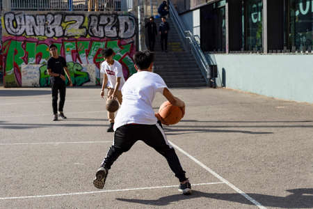 teenagers play street basketball or streetball. Sports, healthy lifestyle and team games in the street of Barcelona, Catalonia, Spain, 30 April, 2019. Editorial