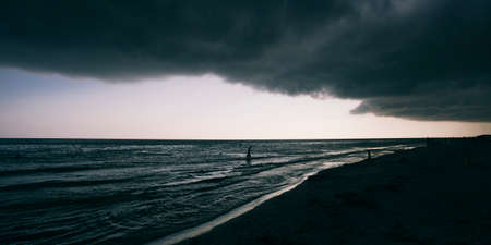 Panoramic widescreen view on the deep blue sea or ocean with dramatic toning on sunset. Big black hurricane clouds. Boundless waving sea. Fascinating and pacifying background.