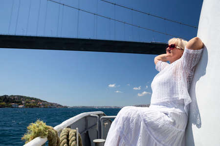 Smiling attractive woman in sunglasses on the big white ship or yacht. Cruise, travel and adventure for active retiree. Beautiful blue sea on the background.