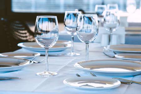 Table setting in restaurant. Empty wine glasses, plates, forks, knifes on the tablecloth. Elegant restaurant interior.