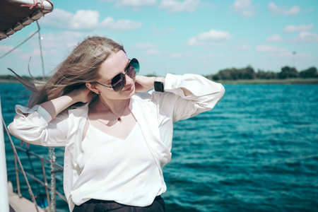 Attractive smiling girl in a white shirt and sunglasses on a yacht. The concept of yachting or cruise on the sea or river. Imagens