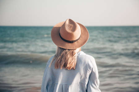 Girl in a straw hat and shirt on the beach. Back view. Blue ocean or sea water on the background. Travel and journey concept.