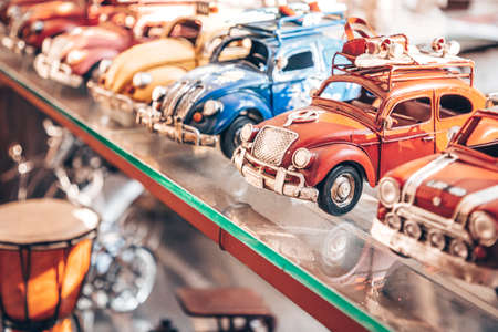 Big collection of retro car models on the shelf. Miniatures of colorful vintage vehicles in the shop. Turkey, Istanbul, 2019-08-18