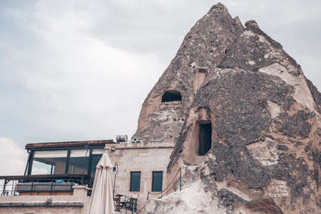 Cave houses and buildings in Cappadocia, Turkey. Stone peaks with doors and windows. Dwelling in real caves.