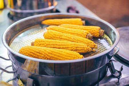 Boiled yellow corn in the pot with hot water. Traditional street food or dish for home meal, bbq. Stockfoto