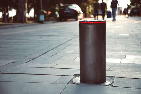 Illuminated retractable automatic traffic bollard protects pedestrian zone. Safety concept. Blurred people on background