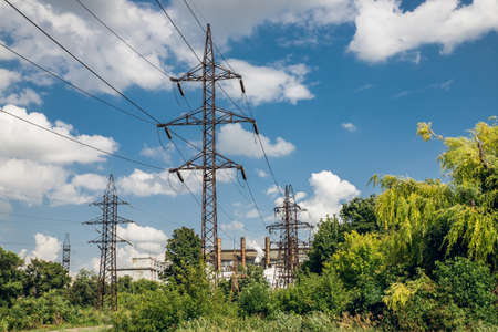 power lines among green grass against blue sky Banque d'images - 130547172