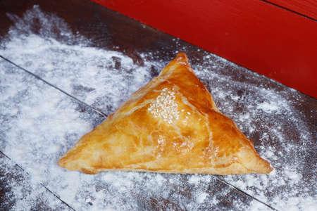 Samsa on a table covered with flour. Samsa - Uzbek national cuisine