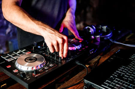 DJ plays live set and mixing music on turntable console at stage in the night club. Disc Jokey Hands on a sound mixer station at club party. DJ mixer controller panel for playing music and partying. Banque d'images