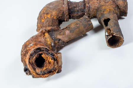 Fragments of old cast-iron water pipes on white background. After many years of operation corroded metal pipe was destroyed. Rusty steel tube with holes of metallic corrosion. Rusty cast iron, metal Imagens
