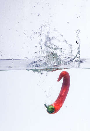 hot chili pepper in the water. splash of water and fruit floating in it. Stok Fotoğraf
