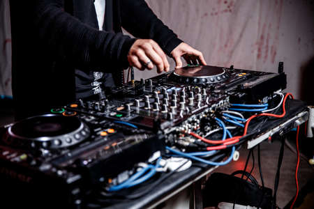 DJ plays live set and mixing music on turntable console at stage in the night club. Disc Jokey Hands on a sound mixer station at club party. DJ mixer controller panel for playing music and partying. Stock Photo