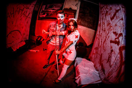 KHARKIV, UKRAINE - OCTOBER 26, 2019: Crazy dead nurse with knife in the hand in a dark room