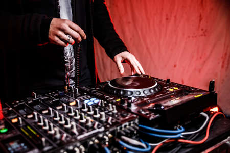 DJ plays live set and mixing music on turntable console at stage in the night club. Disc Jokey Hands on a sound mixer station at club party. DJ mixer controller panel for playing music and partying. Фото со стока