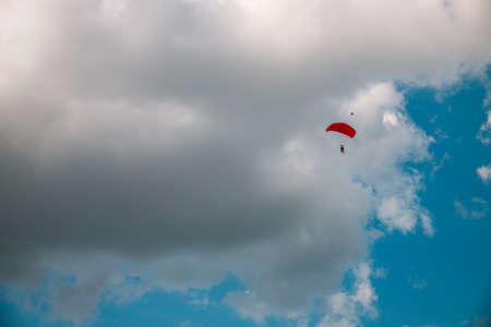 Paratrooper parachuting in blue sky. Military service