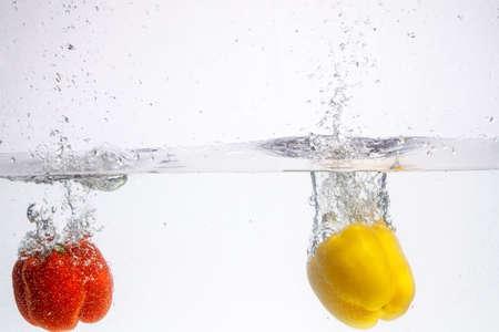 three peppers falling in water Фото со стока