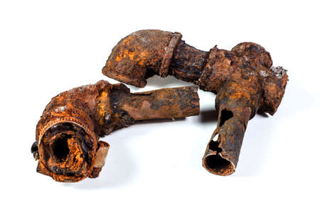 Fragments of old cast-iron water pipes on white background. After many years of operation corroded metal pipe was destroyed. Rusty steel tube with holes of metallic corrosion. Rusty cast iron, metal Фото со стока