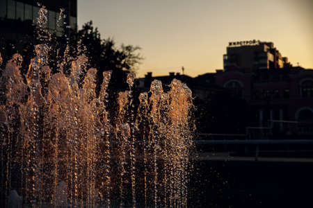 Fountain in the public city park. Sunset in summer.