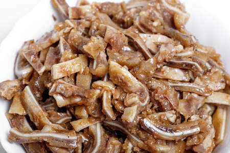Appetizing beer snack - smoked pork pig ears on a board on a gray background