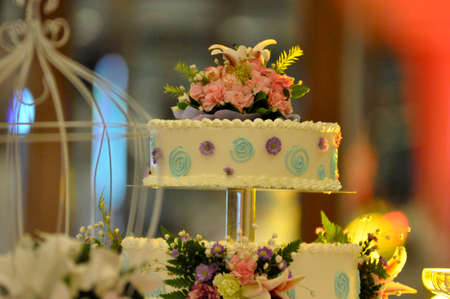 engage: Two tiers wedding cake with colourful cream drawing  around and bunches flower decoration