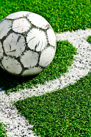 Old soccer ball on green grass