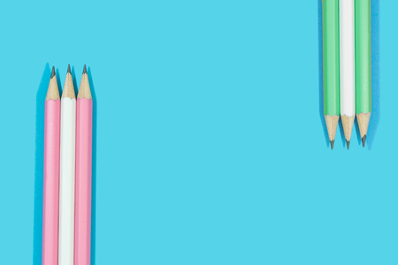 Pencils of pink, white and green on blue background.  Concept education stationery.